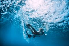 Attractive surfer girl dive underwater with wave. Attractive surfer girl dive underwater with under wave royalty free stock photos