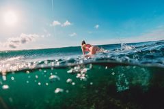 Attractive surfer woman in ocean and wave. Surf girl make duck dive. stock images