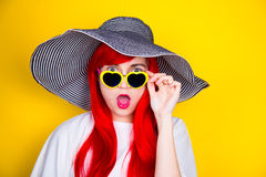 Attractive surprised red-haired young woman in sunglasses and ha Royalty Free Stock Images