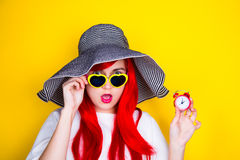 Attractive surprised red-haired young woman in sunglasses and ha Stock Photos