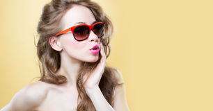 Attractive surprised young woman wearing sunglasses. On gold back Royalty Free Stock Photo