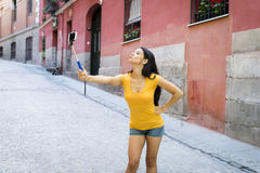 Attractive and sweet latin woman smiling happy taking self portrait selfie photo with mobile phone. Young attractive and sweet latin woman smiling happy taking Stock Image