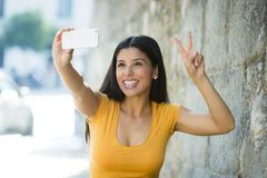 Attractive and sweet latin woman smiling happy taking self portrait selfie photo with mobile phone. Young attractive and sweet latin woman smiling happy taking Royalty Free Stock Image