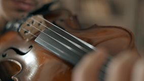Attractive talented young man playing violin sensually. The violinist rehearses close-up 4K stock footage