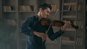 Attractive talented young man playing violin sensually. The violinist rehearses in the interior studio against the stock video