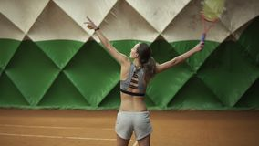 Attractive, tall disabled woman plays tennis, makes a ball pitch. Long haired, in grey shorts and sports bra. Indoors.  stock footage