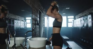 Attractive tall fit blonde woman taking shirt off, looking in the mirror in dark gym locker room exhausted slow motion. Beautiful female athlete overwhelmed stock footage