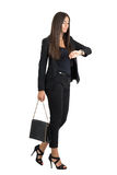 Attractive tanned business woman checking time while walking. Side view Stock Photos