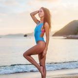 Attractive tanned female tourist in swimwear standing on seashore at seaside resort. Stock Image