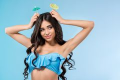 Attractive tanned girl in bikini posing with cocktail umbrellas, isolated on blue stock image