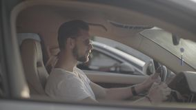 Attractive tattooed handsome young man in sunglasses sitting in luxury sport racing car opposite to rival ready to start. A car race on empty highway road stock footage