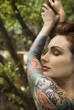 Attractive tattooed woman. Nude tattooed Caucasian woman in forest leaning on tree in Maui, Hawaii, USA Royalty Free Stock Photo