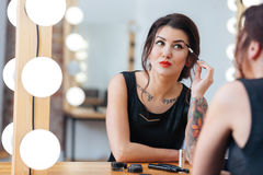 Attractive tattooed woman doing makeup in dressing room Stock Images