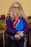 Attractive teacher. Attractive middleaged teacher standing in the classroom with folders in her hands Royalty Free Stock Images