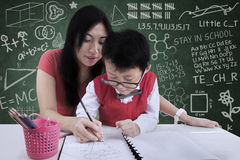 Attractive teacher help a boy to write in class. Attractive female teacher help a boy to write in class stock image