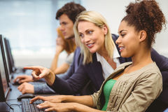 Attractive teacher talking to her student in computer class Royalty Free Stock Photography