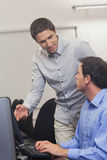 Attractive teacher talking to his student in computer class Royalty Free Stock Photos