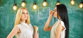 Attractive teachers overworking after classes. Ladies ready to start private lesson, chalkboard on background. Teachers. In formal wear with book and glasses royalty free stock photography