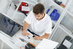 Attractive technician calculating quote at clients home. Kitchen stock image