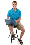 Attractive Teen Boy with Laptop. Cute freckled male teen sitting on stool with laptop. Shot with Canon 20D Stock Photo