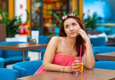 Attractive teen girl drinking juice in bar Royalty Free Stock Photography