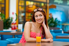 Attractive teen girl drinking juice in bar Royalty Free Stock Images