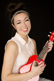 Attractive teen girl model playing a ukulele smiling Royalty Free Stock Images