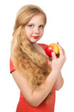 Attractive teen girl in the orange t-shirt holding an red apple Royalty Free Stock Photos