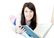 Attractive teen girl studying lying on a bed Royalty Free Stock Images