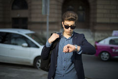 Attractive teenage boy looking at his watch and carries a backpack Royalty Free Stock Image