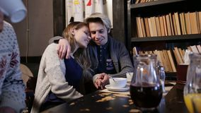 Attractive teenage couple in love in cafe hugging stock video