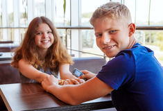 Attractive teenage couple sitting in cafe Stock Images