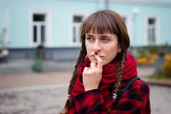 Attractive teenage girl deliberates a decision. On street background Stock Image