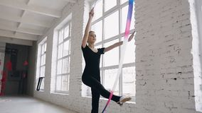 Attractive teenage girl gymnast dancing with colored ribbon in sport gym in white background near windows. Attractive. Girl gymnast jumping with ribbon in sport stock footage