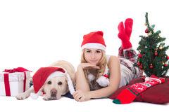 Attractive teenage girl in pajamas lying with dog in santa hat i Royalty Free Stock Photo