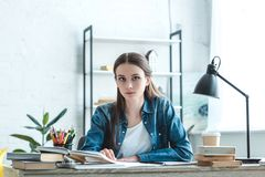 Attractive teenage girl sitting at desk and looking at camera while studying. At home royalty free stock images