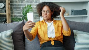 Teenage girl taking selfie with smartphone camera sitting on sofa at home. Attractive teenage girl is taking selfie with smartphone camera sitting on sofa at stock footage