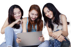 Attractive teenage girls using laptop in studio Stock Photography