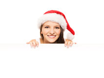 Attractive teenager girl in a Christmas hat with a blank billboard Stock Photo