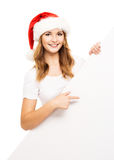 Attractive teenager girl in a Christmas hat with a blank billboard Stock Photos