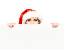 Attractive teenager girl in a Christmas hat with a blank billboard Royalty Free Stock Photos