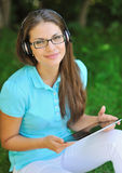 Attractive teenager listening music through headphones holding l Stock Images