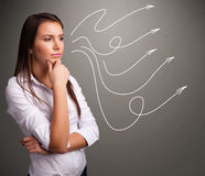 Attractive teenager looking at multiple curly arrows Royalty Free Stock Photo