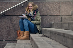 Attractive teenager sitting on steps in town Stock Photo