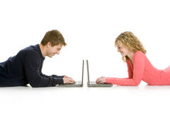Attractive teenagers lying down using lap tops Royalty Free Stock Photos