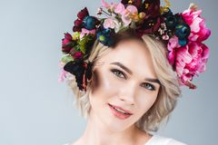 Attractive tender girl posing in wreath with beautiful butterfly on cheek,. Isolated on grey royalty free stock image