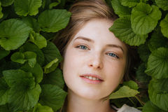 Attractive tender young woman surrounded by green leaves Royalty Free Stock Photography