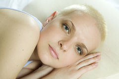 Attractive thoughtful blond bald woman lying Stock Photography
