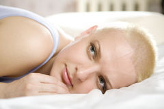 Attractive thoughtful blond bald woman lying Royalty Free Stock Photo