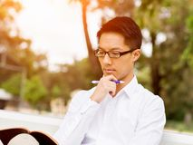 Attractive thoughtful businessman sitting on bench and writing in notepad Stock Photo